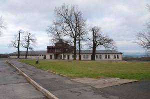 Bâtiment de l'entrée principale et sa porte en fer forgé (1938) portant l'exergue « Jedem das Seine » (à chacun son dû). Le commandant a voulu qu'elle soit lisible depuis l'intérieur. Les prisonniers rassemblés sur la place d'appel devaient ainsi l'avoir devant les yeux. Le site du mémorial de Buchenwald (http://www.buchenwald.de) explique que cette inscription remonte à la maxime juridique, datant de deux mille ans « suum cuique » : « Iuris praecepta sunt haec: honeste vivere, alterum non laedere, suum cuique tribuere. » - « Les principes fondamentaux du droit sont les suivants : vivre honnêtement, ne faire de tort à personne, donner à chacun son dû. »